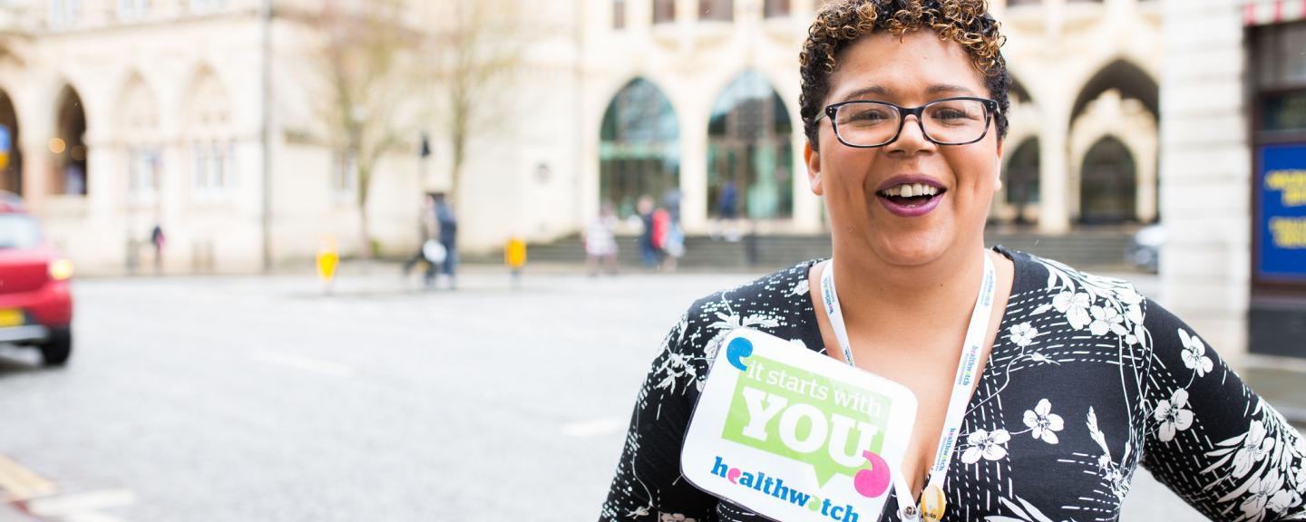 Healthwatch staff member holding an It Starts With You sign to promote the campaign
