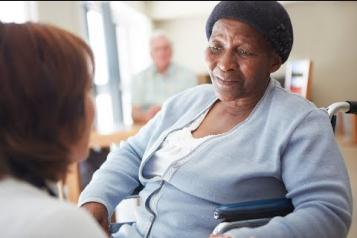 Black elderly woman ina nursing home being spoken to by a nurse