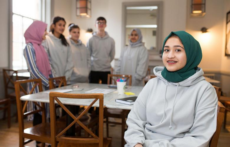 Young volunteer wearing a headscarf sitting down with a group of other young volunteers behindlunteers with one